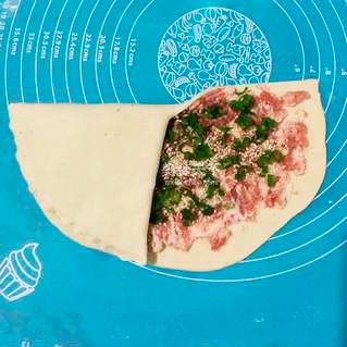 Процесс заворачивания теста для слоёного пирога с мясом.